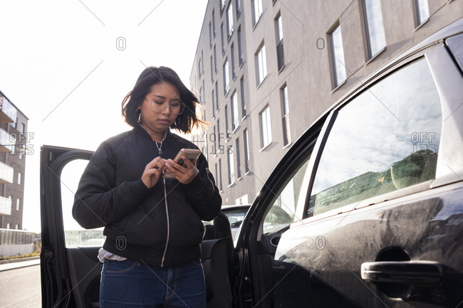 Woman standing by car and using cell phone