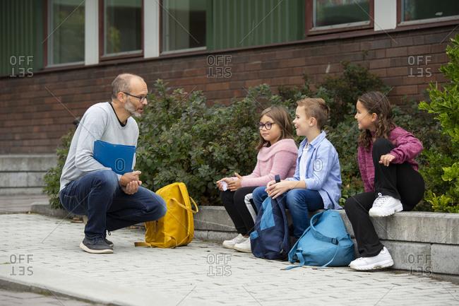 Teacher talking with children in front of school