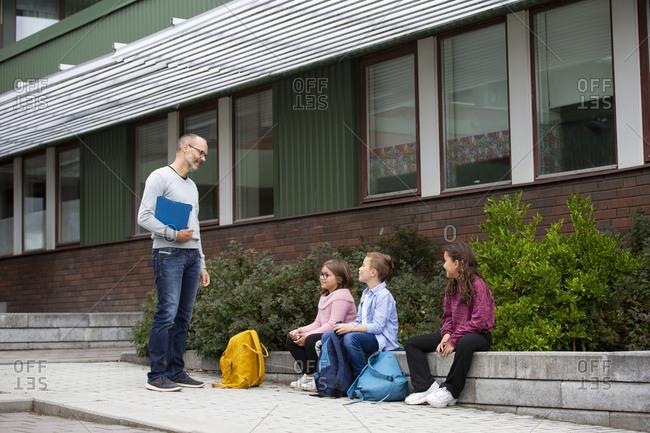 Teacher talking to schoolchildren in front of school