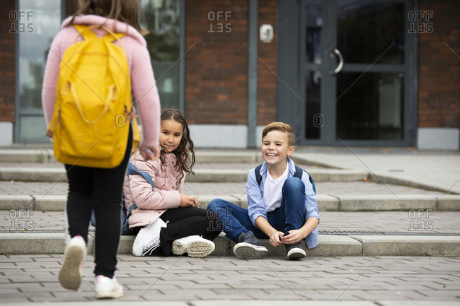 Boy and girl sitting in front of school