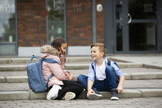 Boy and girl talking in front of school