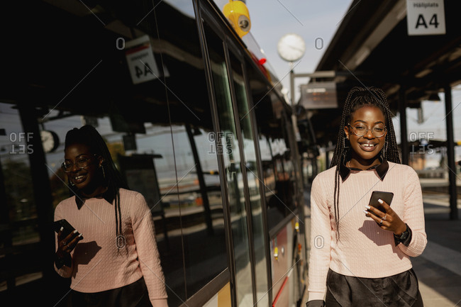 Young woman using cell phone at bus station