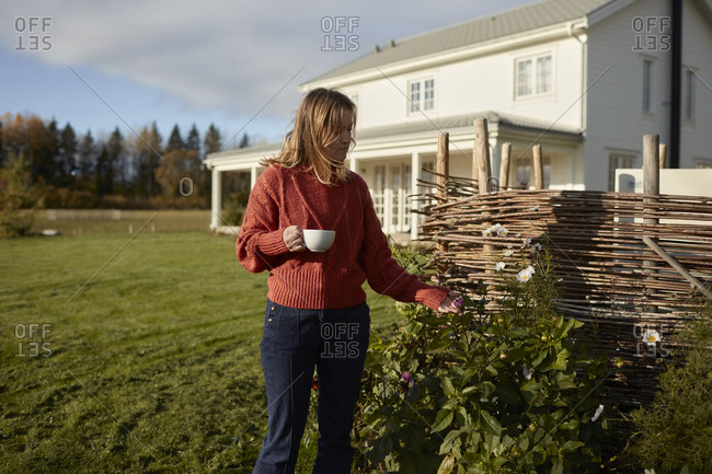 Young woman standing in garden and drinking coffee