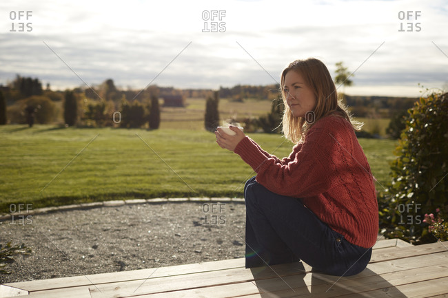 Young woman sitting on porch and drinking coffee