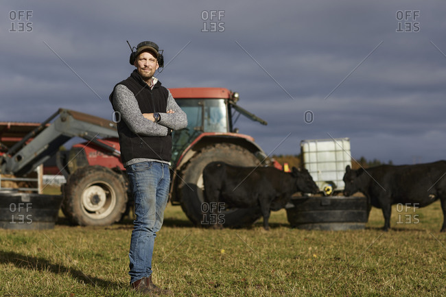Farmer standing in field with tractor in background