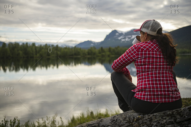 Woman sitting at lake and looking at view