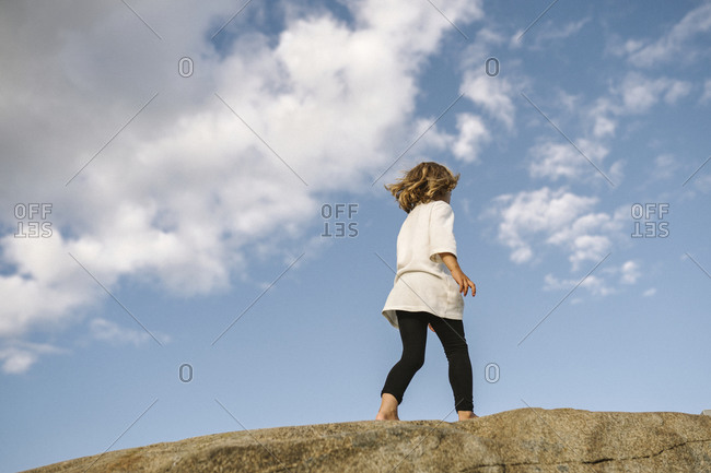Low angle view of girl walking on rocks