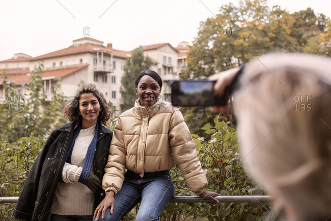 Woman taking picture of female friends by cell phone