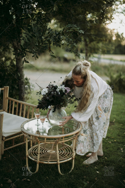 Woman putting vase with flowers on table in garden