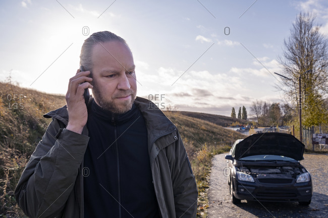 Man using cell phone, broken down car in background