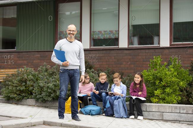 Smiling teacher in front of school, schoolchildren in background