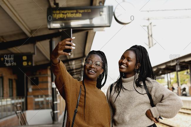 Smiling female friends taking selfie at train station platform