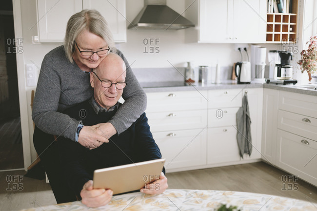 Smiling couple embracing and using tablet at kitchen table