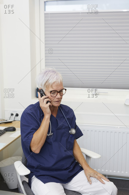 Female doctor talking via mobile phone in her office