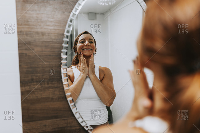 Reflection of woman massaging her face in front of mirror