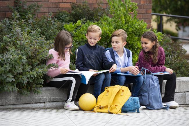 Children looking at school books in front of school building