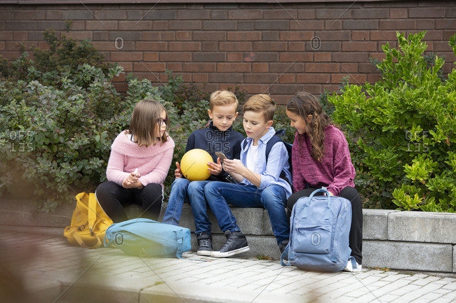 Children looking at cell phone in front of school building