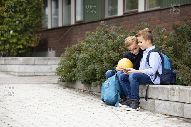 Boys looking at cell phone in front of school building