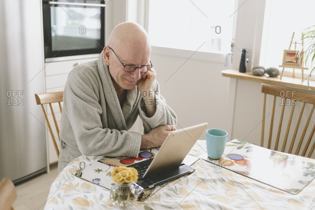 Man sitting at table and having video chat on tablet