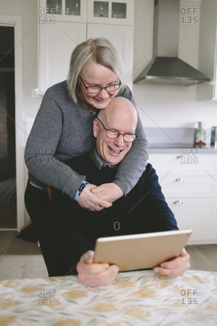 Smiling couple embracing and having video chat on tablet at kitchen table