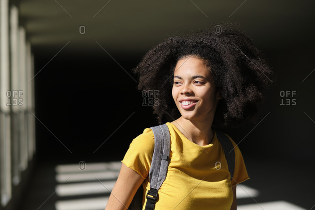 Smiling student with bag looking away while standing at university corridor
