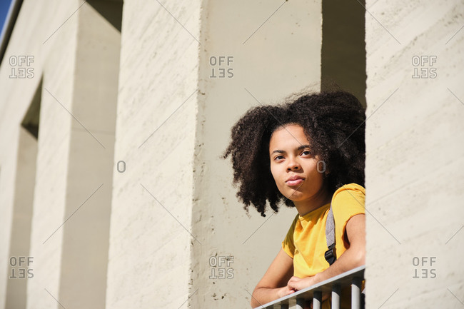 Student looking away while leaning on railing at university