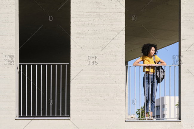 Smiling young student looking away while leaning on railing at university