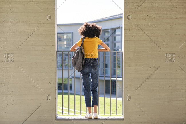 Female student carrying bag while leaning on railing at university