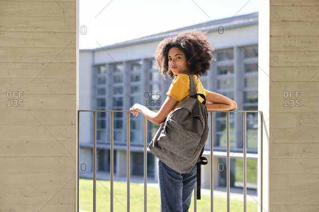 Student with bag staring while leaning on railing at university