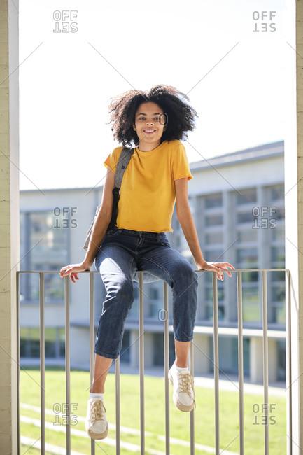 Smiling woman sitting on railing at university