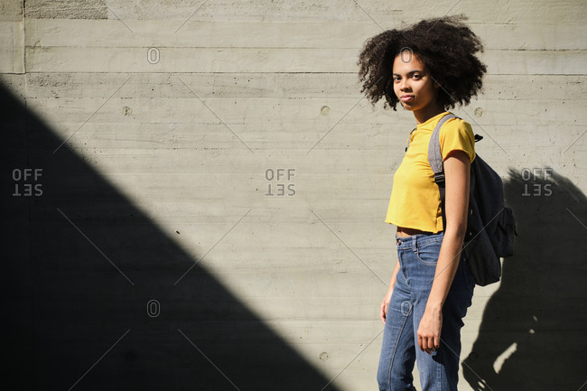 Young student with bag standing against wall