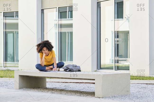 Student writing in book while sitting on bench at university campus