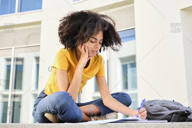 Curly hair student studying while sitting at university campus
