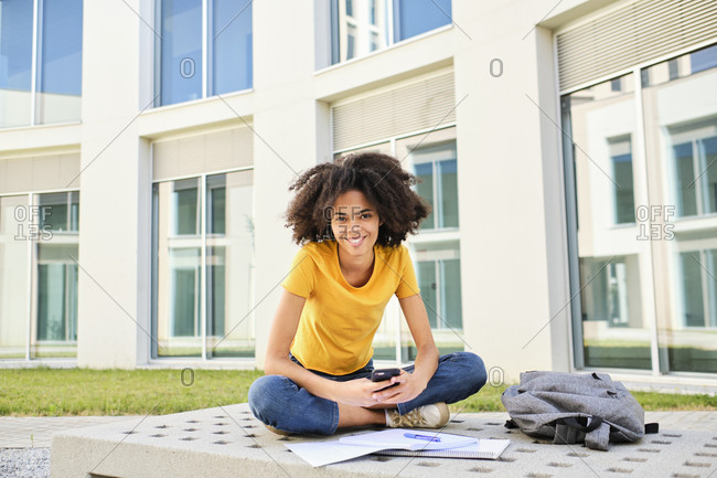 Smiling student with books using mobile phone while sitting at university campus
