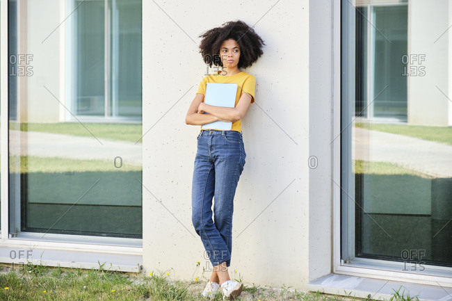 Female student holding book while leaning on wall at university campus