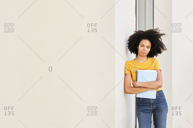 Young university student with book staring while leaning on wall