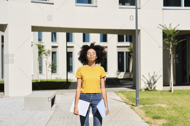 University student holding books while standing with eyes closed at university