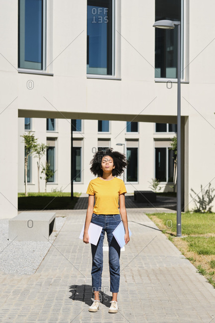 Young student holding books while standing with eyes closed at university
