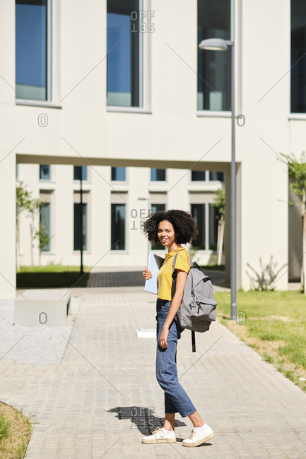 Smiling student holding book while standing at university campus