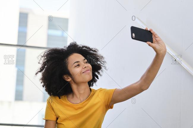 Smiling student taking selfie through mobile phone while sitting at university