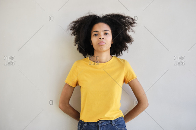 Young student standing with hands behind head against wall
