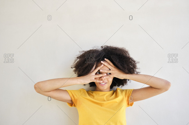 Frustrated student with head in hands standing against white wall