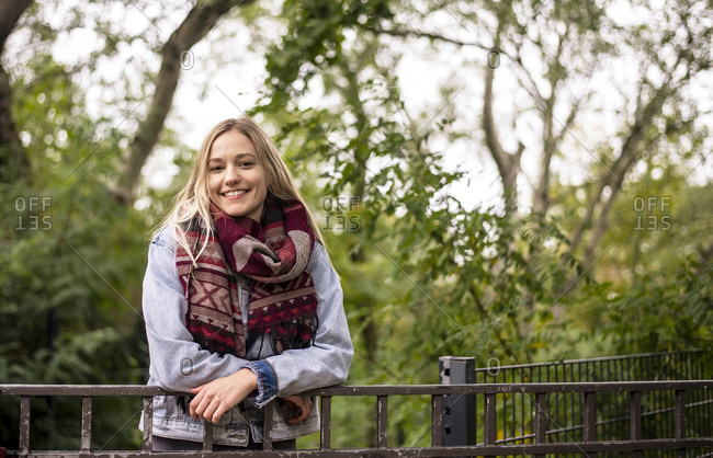 Smiling woman leaning on railing in autumnal park