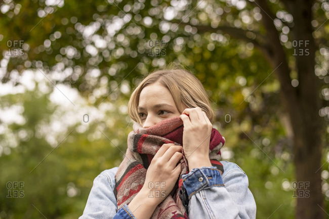 Young woman covering face with scarf in park
