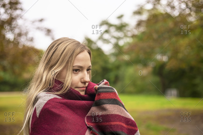 Young woman wrapped in scarf at park during autumn