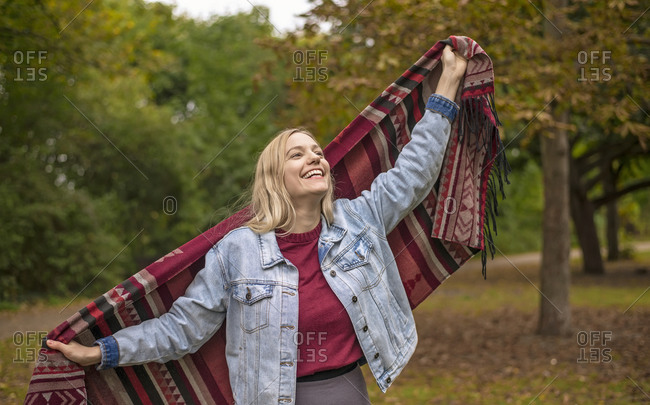 Happy woman with scarf standing in autumnal park