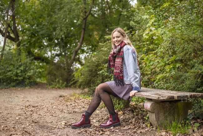 Attractive woman sitting on bench in autumnal park
