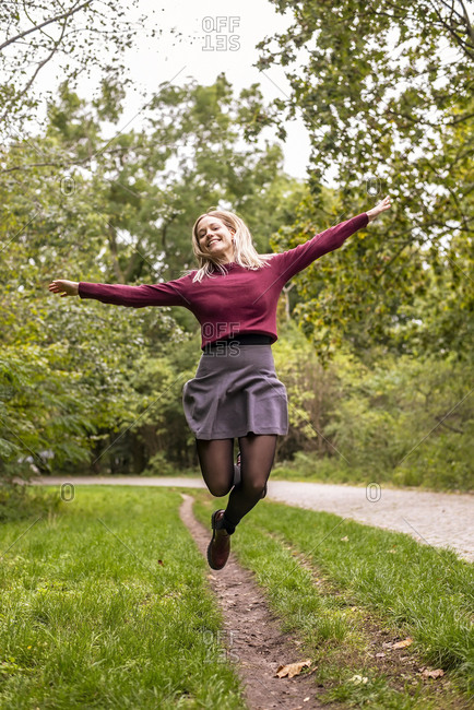 Young woman with arms outstretched cheerfully jumping in park