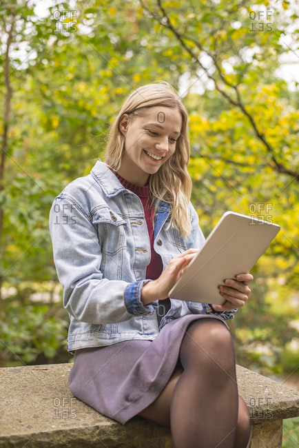 Smiling woman using digital tablet in autumnal park