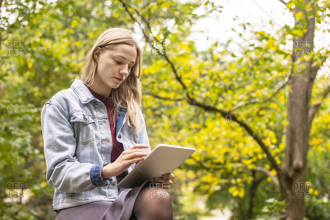 Young woman using digital tablet in park during autumn